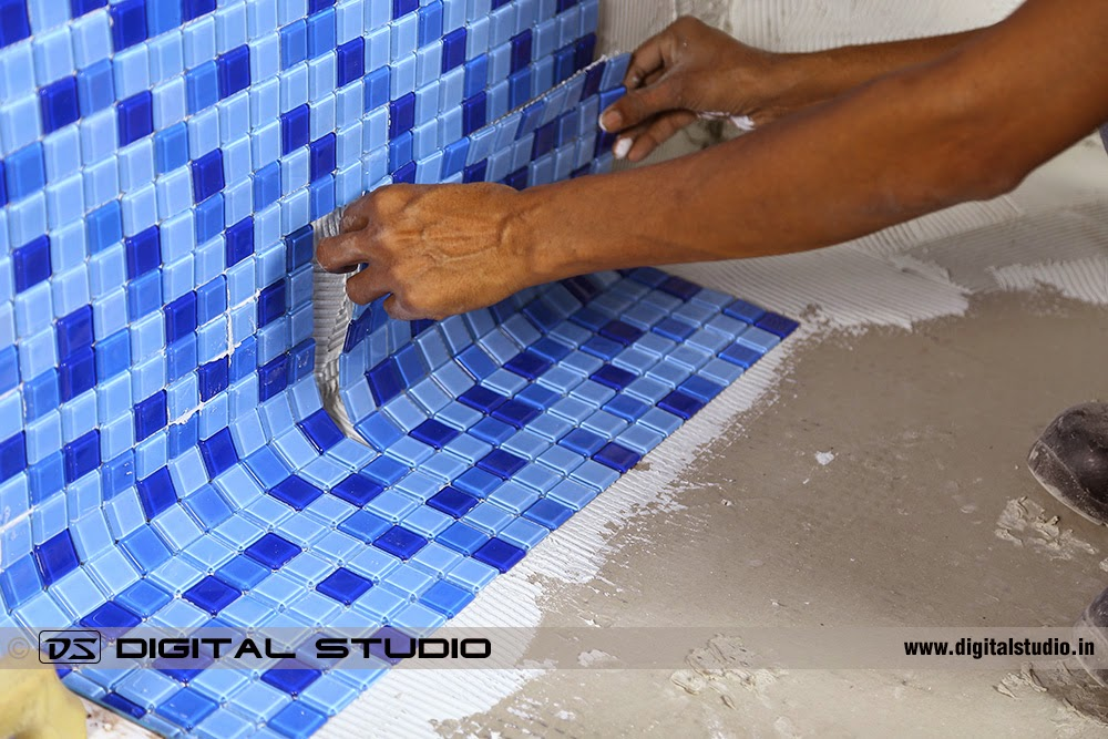 Mason working on putting swimming pool tile