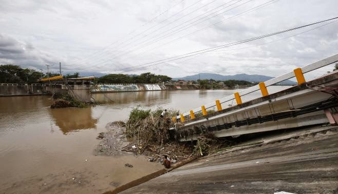 A worker clears debris on a bridge destroyed during the onslaught of Typhoon Rammasun, (locally named Glenda) in Batangas city south of Manila, July 17, 2014. (Credit: Reuters/Erik de Castro) Click to enlarge.