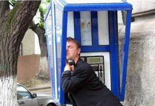 funny picture: man sleeps in a phone booth