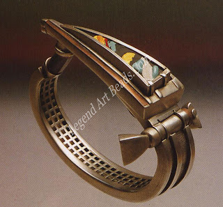 This metal bracelet was mainly fabricated in silver and has some red gold added for contrasting color. Some of the sections were cast and then set or soldered onto the main piece. The decorative top section is an unusual mixture of enamel and porcelain. The hinge and catch have been cleverly integrated into the design of the piece