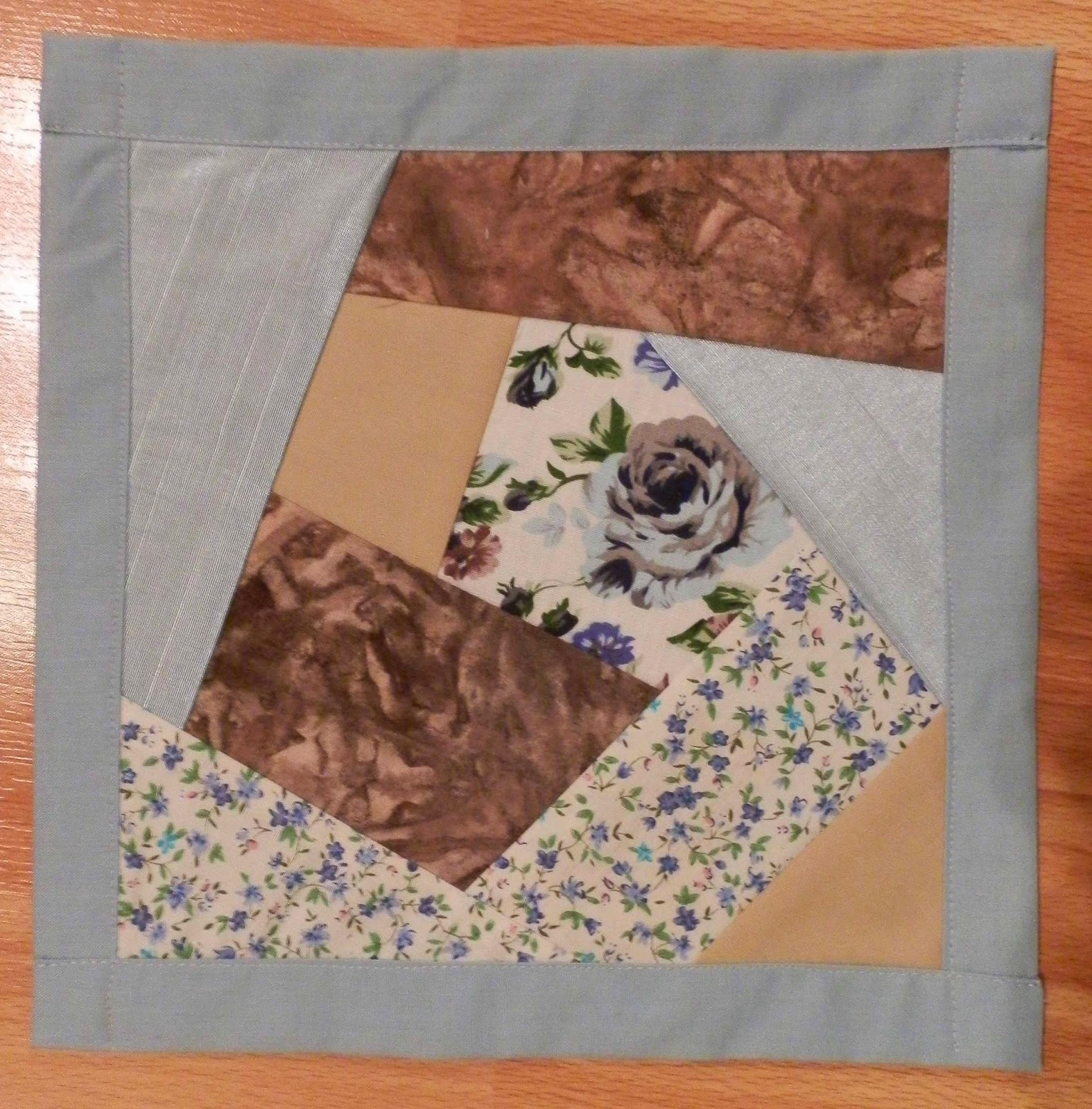 block of crazy quilting style patchwork in blue and brown fabrics with large blue rose in centre