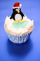 Winter theme cupcake topped with buttercream snow and a fondant penguin cake topper