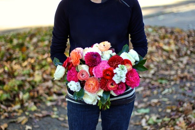 Bouquet by Sweet Pea Floral Design Detroit Ann Arbor A Fall bridal bouquet featuring garden roses including coral romantic antike dark pink baroness and ivory white david austin patience garden roses.  Ranunculus including peach pink coral red and white accented with scabies, plum ball dahlia and camellia foliage for Grosse Pointe Yacht Club wedding