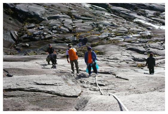 登山扶着绳索攀爬