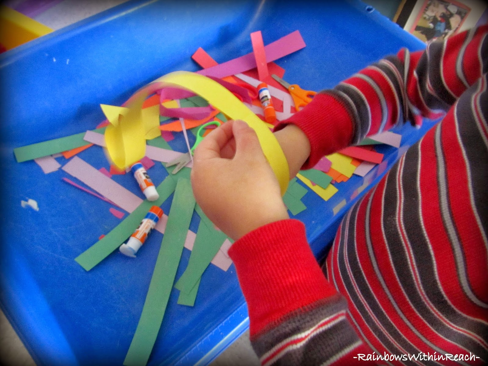 Sensory Table filled with strips and stripes of paper, scissors & glue sticks! (via RainbowsWithinReach)