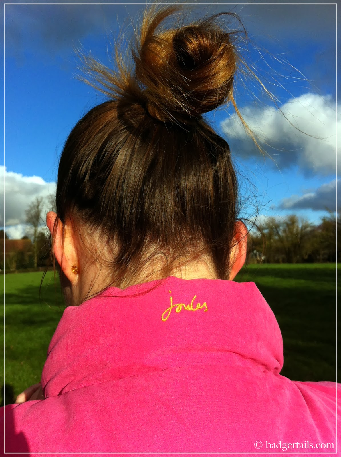 brunette lady wearing pink joules gilet in english countryside field