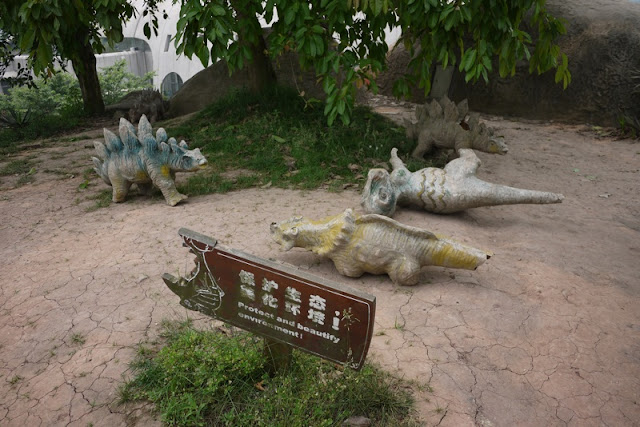 several small models of dinosaurs that are in various states of decay or knocked over