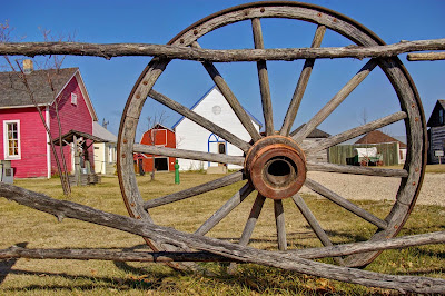 Pioneer village as seen through a wagon wheel