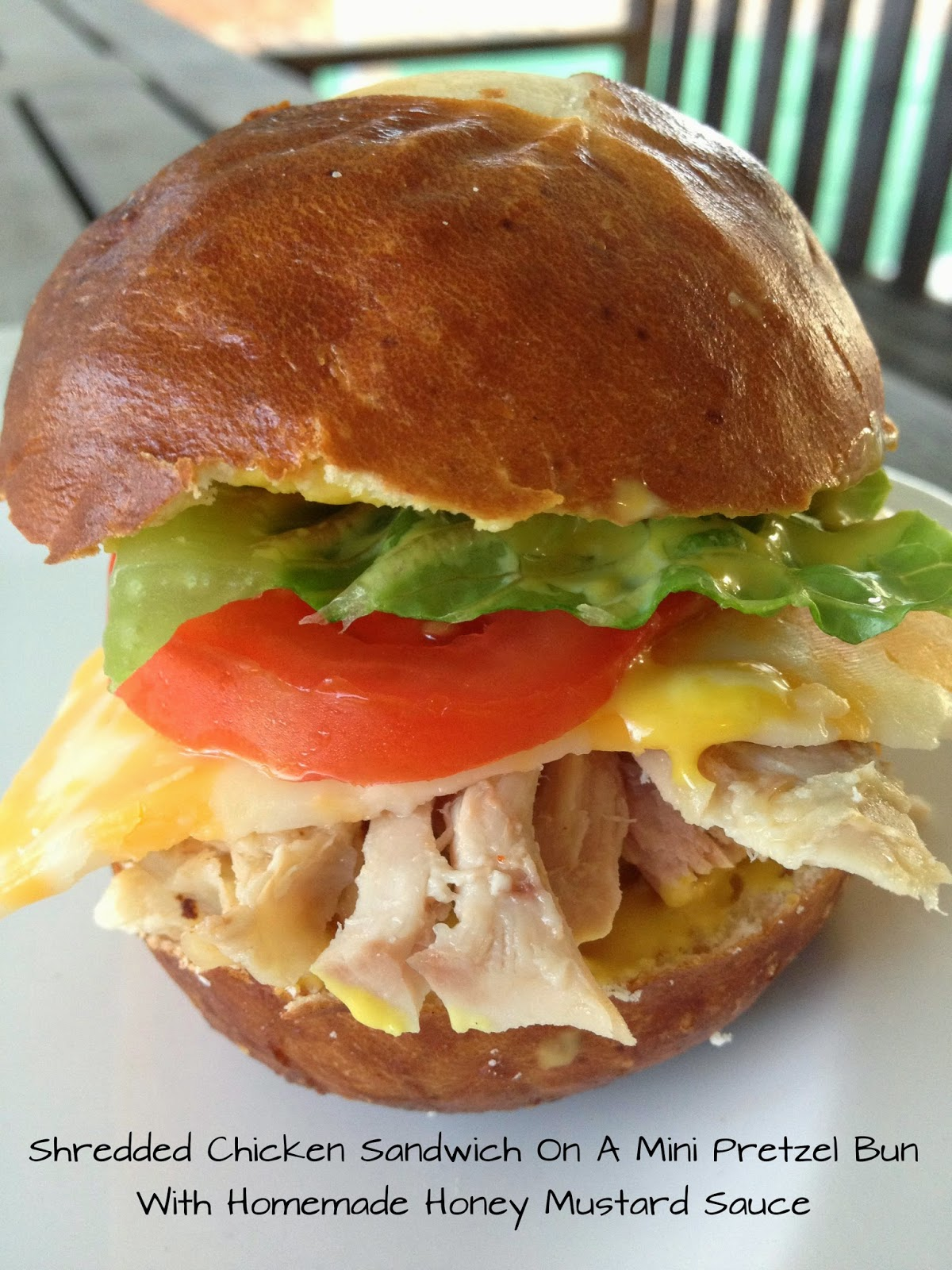 Shredded Chicken Sandwich On A Pretzel Bun With Homemade Honey Mustard