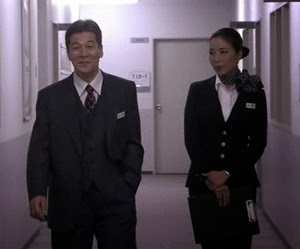 Inoue Jun ( 井上順 )  (いのうえ じゅん ) as Director Dazai Sinichiro, talks to Mikami in the corridor.