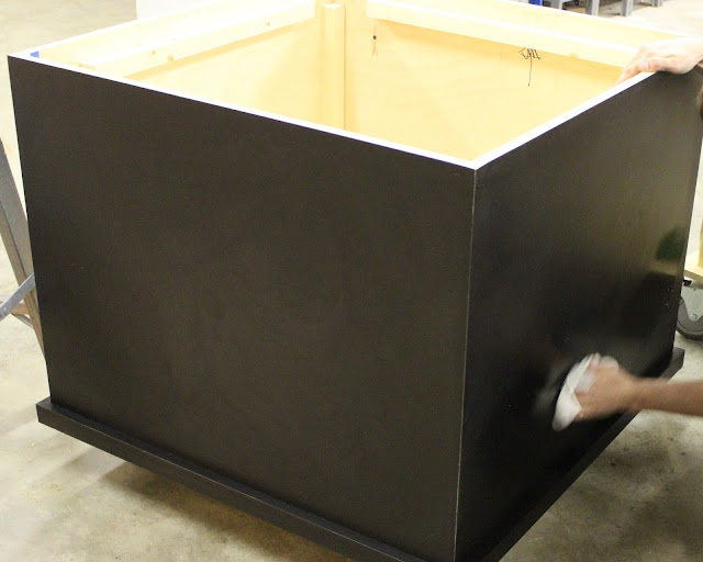 A young man's hands can be seen holding a white rag and carefully wiping down the black laminate of the casework; preparing it to roll out on the floor.