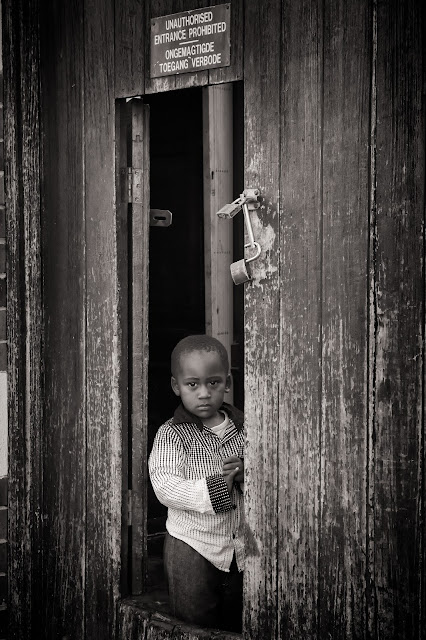 A young boy stands in an old wooden doorway in this street photograph from Cape Town South Africa