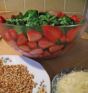 Bowl of greens and strawberries, plates of pine nuts and Parmesan