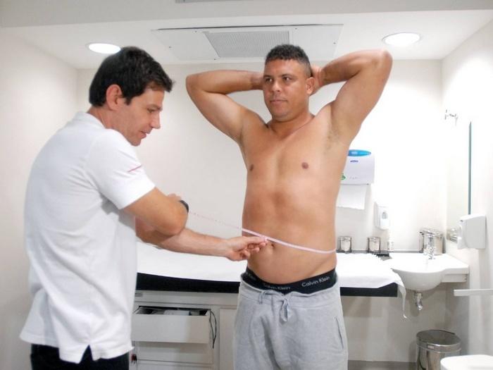 Após três meses de dieta e exercícios físicos, Márcio Atalla mede a cintura de Ronaldo. Foto: TV Globo/Divulgação