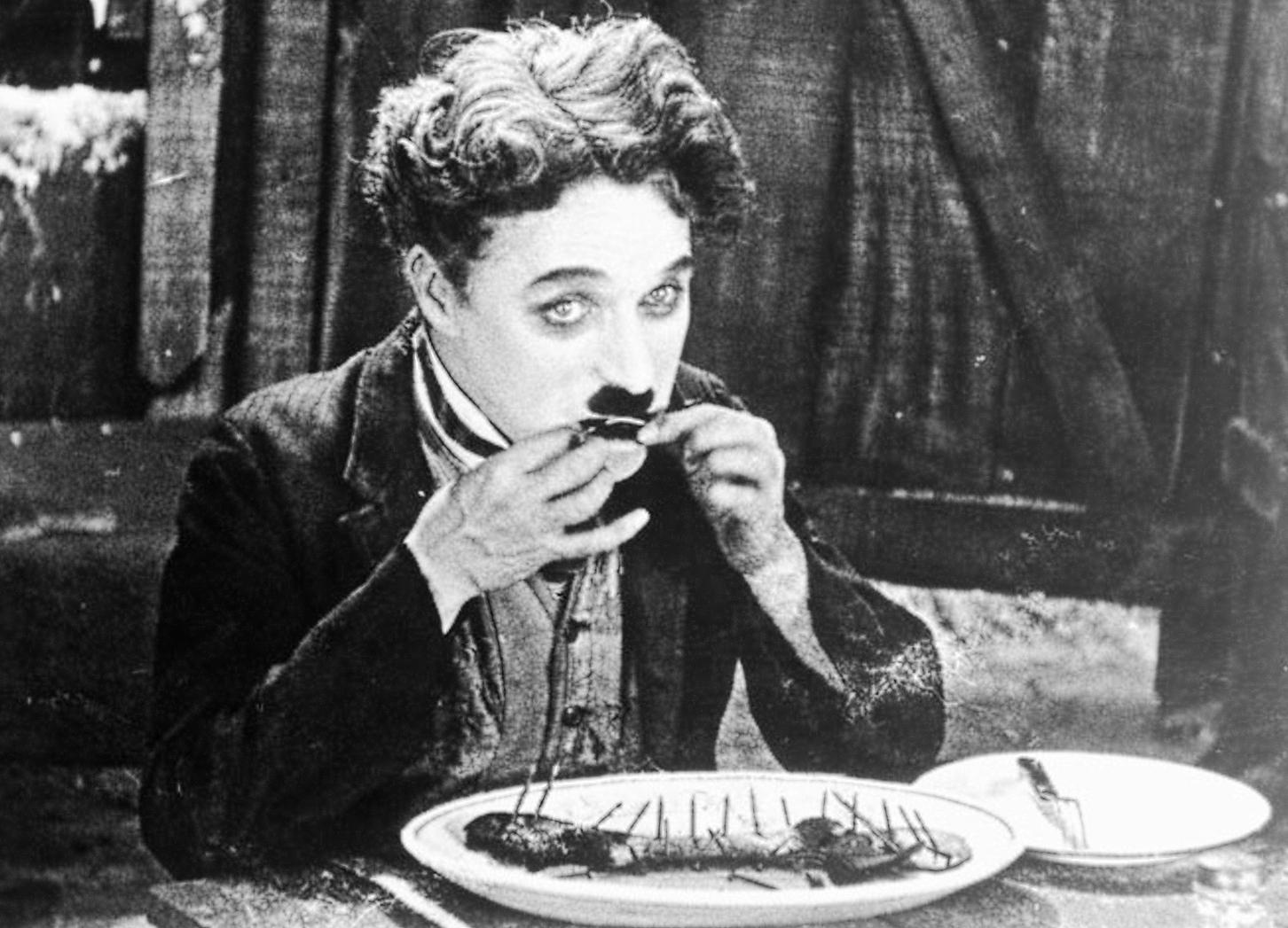 Famoso Fotograma de la película : The Gold Rush en el que podemos ver a Charlot comiéndose una bota