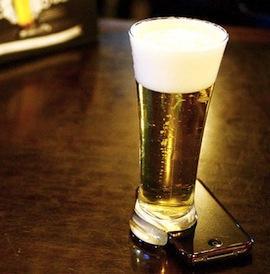 Foto de um copo de chopp que teve seu apoio serrado, encaixando perfeitamente em um iPhone para poder se manter em pé, sobre a mesa.