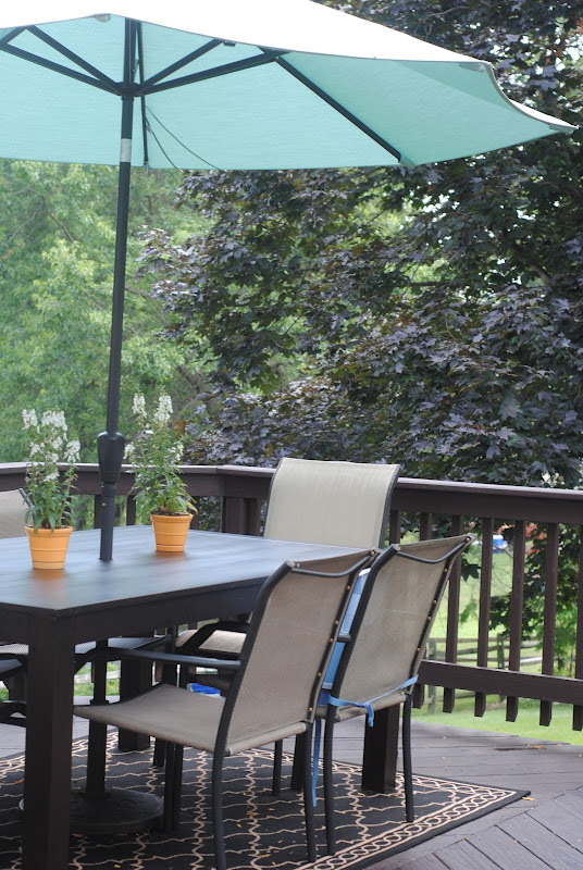 dining table on deck with blue umbrella
