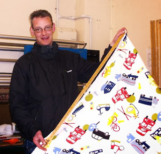 A happy proprietor with a welcoming smile holding attractive well priced fabric.