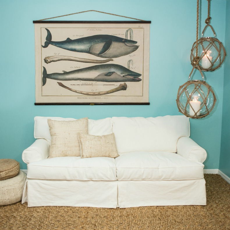 white slipcover montauk sofa with whale hanging art and glass and rope balls in a coastal space