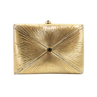 Vintage 1980's Judith Leiber gold clutch with hidden chain strap and onyx stone in the center of a starburst embossed design.