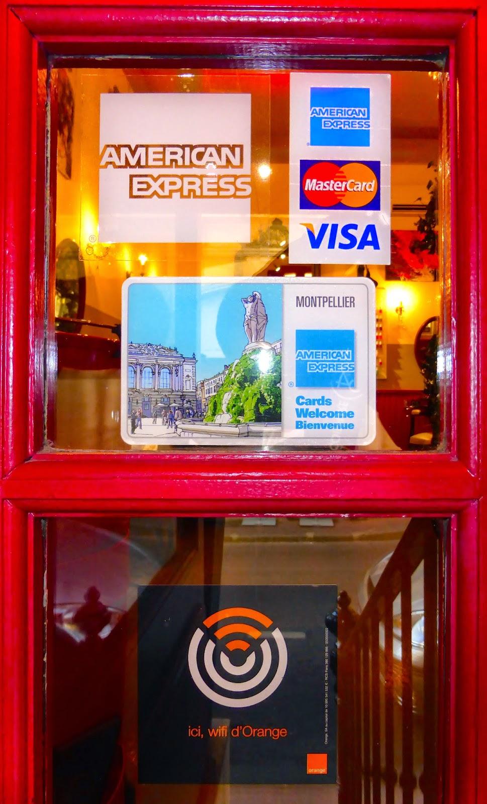 Les visuels d'affiliation au réseau American Express apposés sur la vitrine du Studio 54, salon de coiffure à Montpellier.