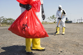 Men in protective suits walk on the beach carrying biohazard bags.