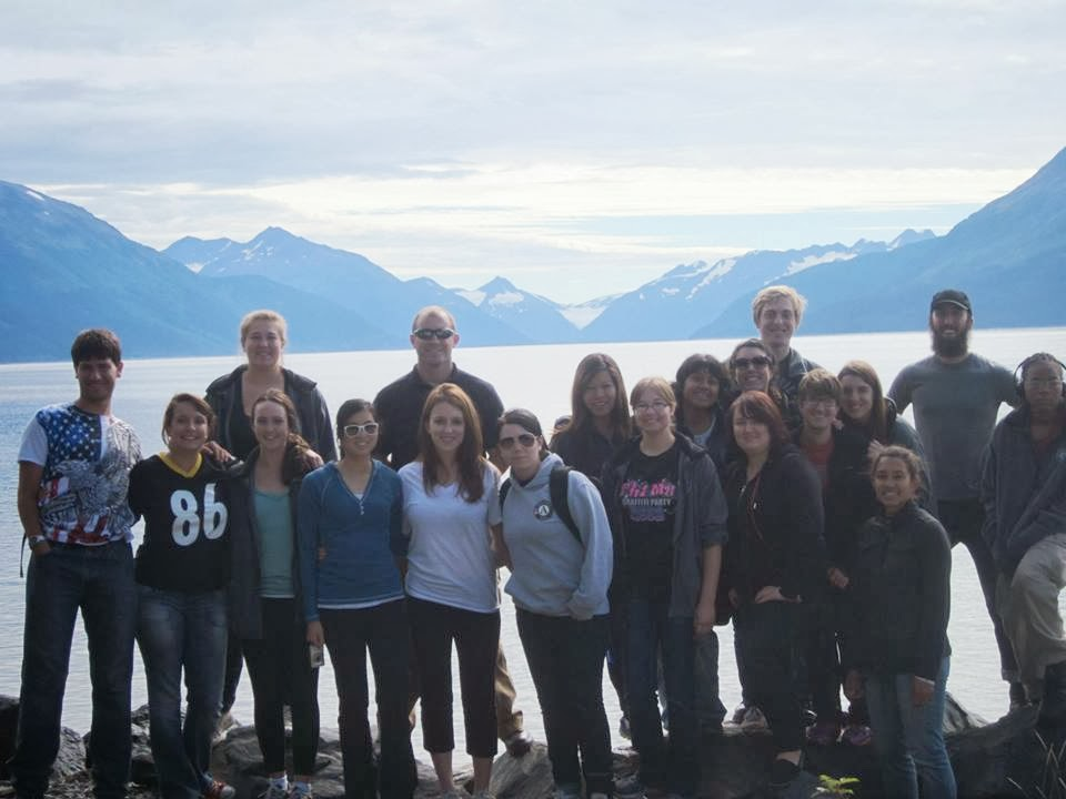 Team picture by a glacier lake with moutain range in background