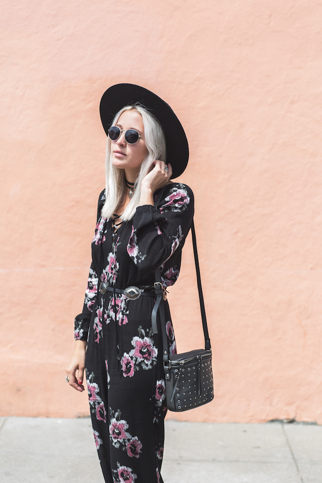 How to style a bohemian jumpsuit by Fashion Style Blogger Bryn Newman of Stone Fox Style. Fringe jacket with fringe sleeves, concho belt, studded bag, and wide brim hat.