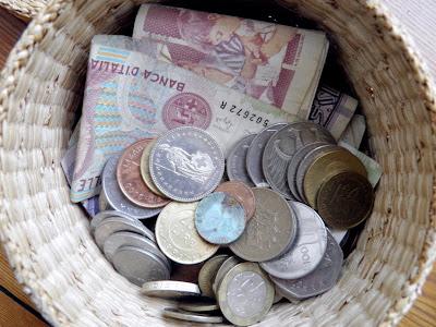 Ein Flechtkorb mit alten europäischen Münzen und Geldscheinen darin
