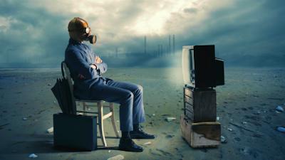 Man in gas mask watching TV