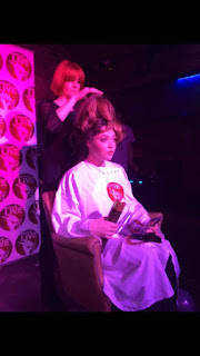 Louise Chrystal on stage styling her models hair for the open chair night