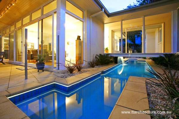 Arquitectura de casas moderna casa con piscina bajo un for Piscina interior casa