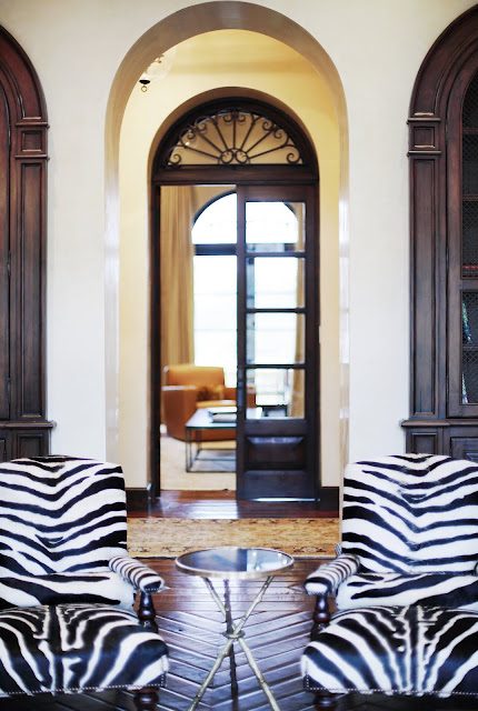 Close up of the zebra print chairs in a living room with herringbone wood parquet floors and neutral furnishings