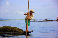 Hombre birmano sobre barca de madera en el Lago Inle