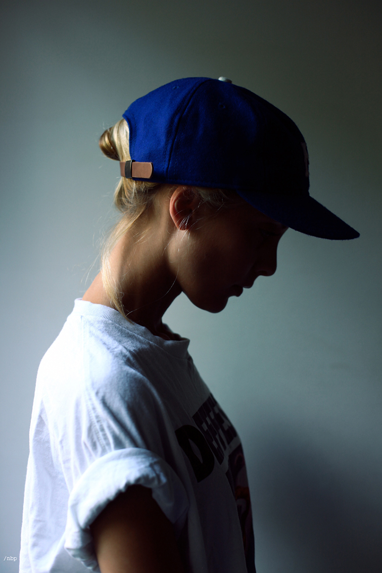 Tomboy style, blond hair tucked into a baseball cap, girl next door, loose tee