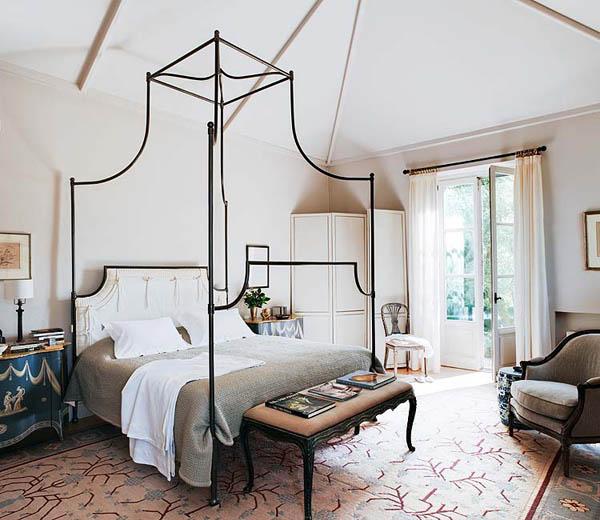 dormitorio con cama con dosel de hierro forjado
