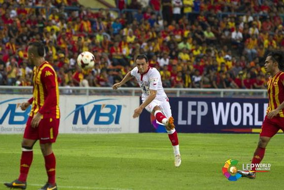 Sevilla player Piotr Trochowski shoots to score a goal against Selangor