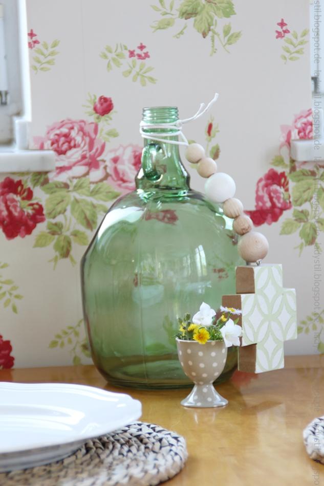grüne-Flasche-auf-holzfarbenem-küchen-tisch