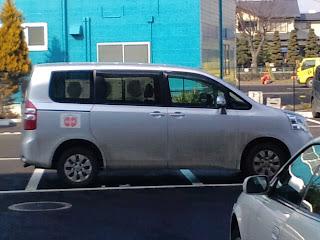 写真:クリニックのロゴマーク付きワンボックスカー