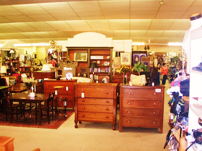 antiqes at an antique mall, lots of wood chest and tables and lamps and pictures and plates