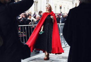 A Modern Red Riding Hood stands before the paparazzi in a beautiful red cape.