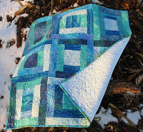 blue batik quilt on woodpile at Freemotion by the River