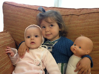 Niña con hermana pequeña y muñeca.