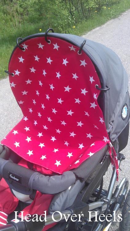 Punainen tähtivaunuverho suojaa taaperon päiväunia