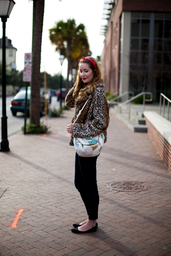 College of Charleston student wears a red bandana to tie her hair as well as an animal print fur coat and slim black jeggings and black flats.