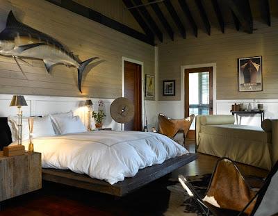 stuffed fish, masculine bedroom, tailored bedding, warm interiors, art in the bedroom