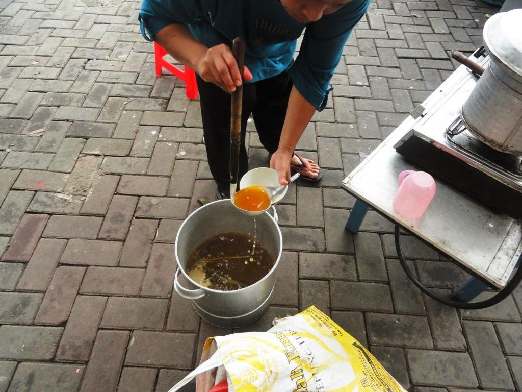 Seorang ibu sedang membuat minuman Adon-adon Coro pesananku