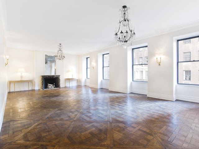 Living room with parquet wood floors, chandeliers and a fireplace