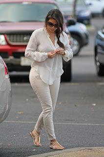Kim Kardashian buttoning her shirt