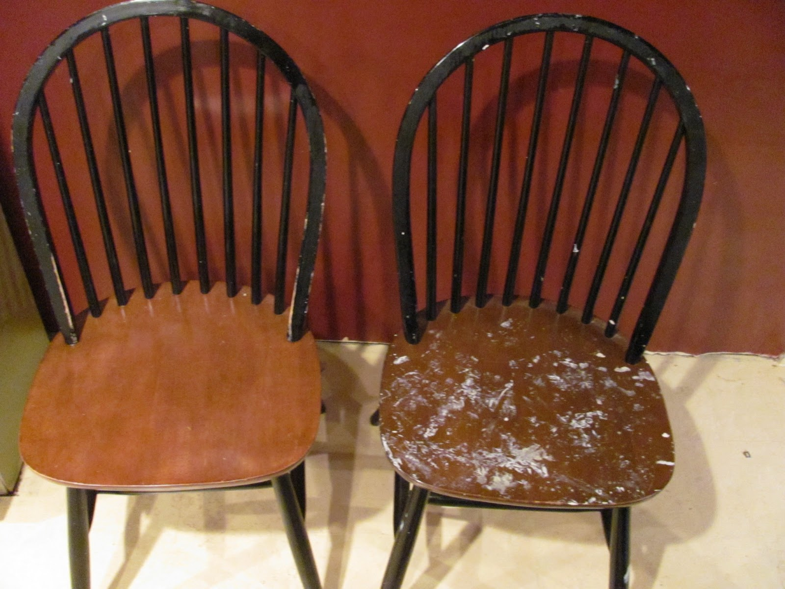 Two wooden chairs on display before being sold. One chair is covered with white paint spots